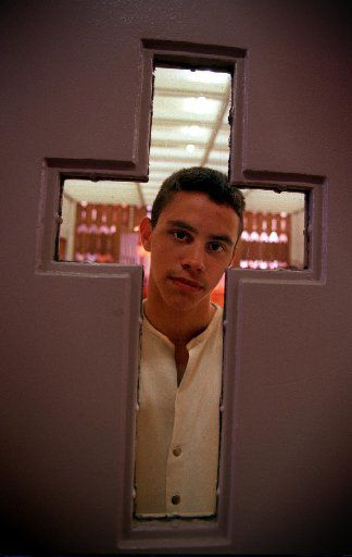 Inmate Ryan Burkhalter, a participant in the 'Youthful Offender Program' at the Clemens Unit, looks out the chapel door window at the prison in Brazoria on December 5, 1999.