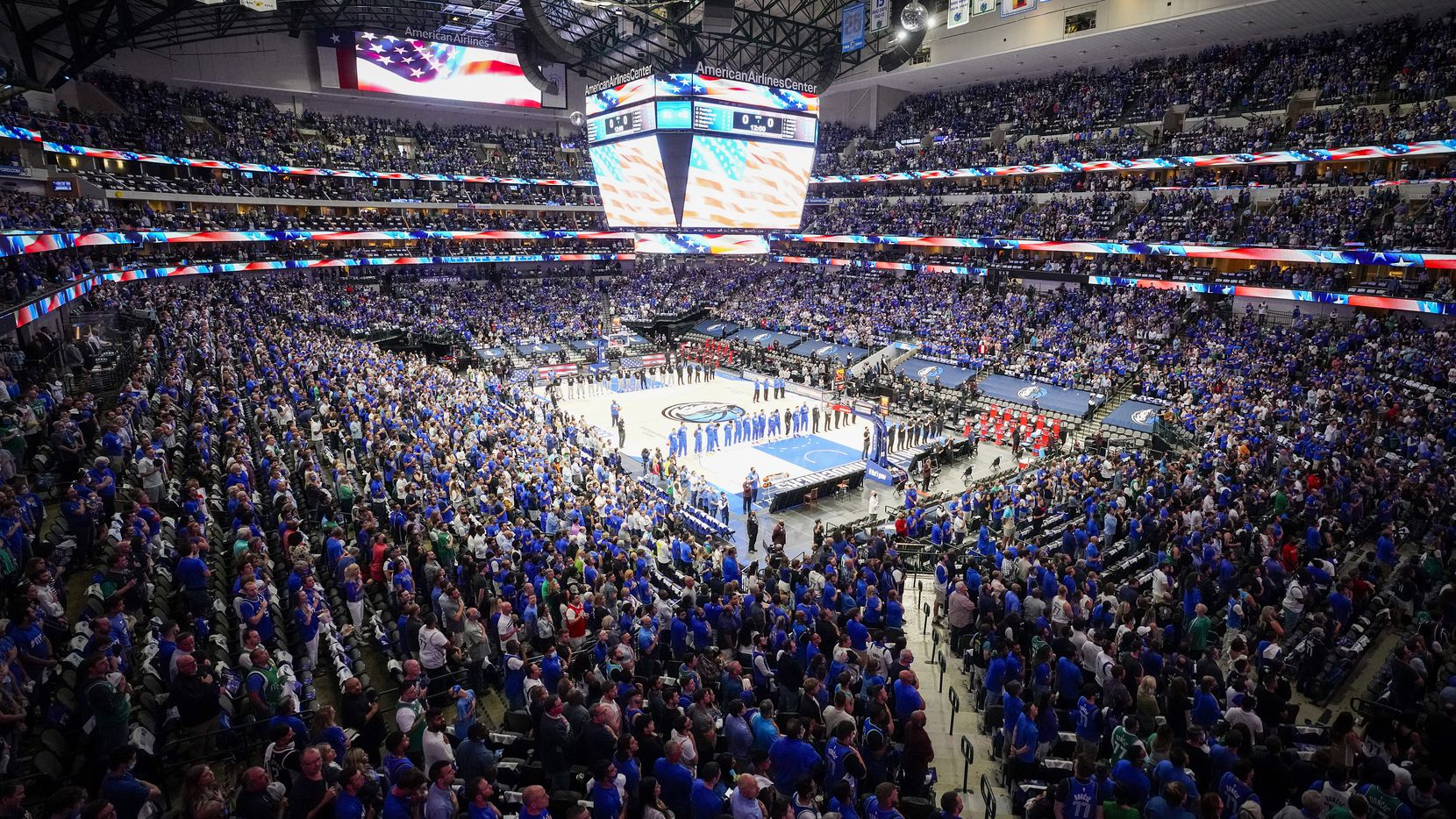 Dallas Mavericks players and fans stand for the national anthem before an NBA playoff basketball game against the LA Clippers at the American Airlines Center on Friday, June 4, 2021, in Dallas.