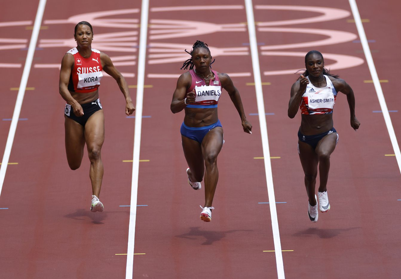 Switzerland's Salome Kora, USA's Teahna Daniels and Great Britain's Dina Asher-Smith compete in the  women's  100 meter race during the postponed 2020 Tokyo Olympics at Olympic Stadium, on Friday, July 30, 2021, in Tokyo, Japan. Daniels finished with a time of 11.04 seconds to advance to the next round. (Vernon Bryant/The Dallas Morning News)