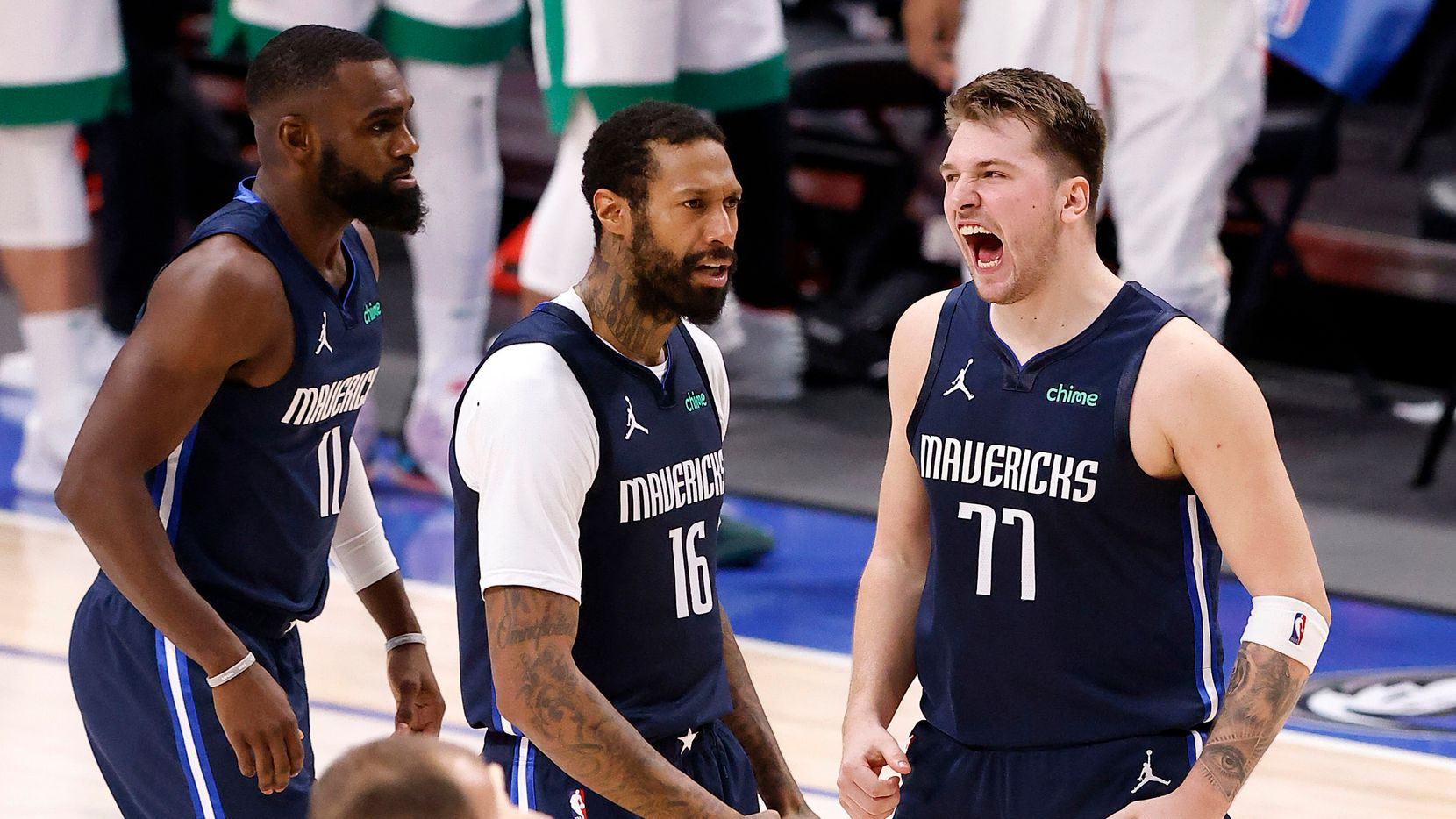 Mavericks guard Luka Doncic (77) celebrates his game-winning shot with forward James Johnson (16) at the end of a game against the Celtics in American Airlines Center in Dallas on Tuesday, Feb. 23, 2021.