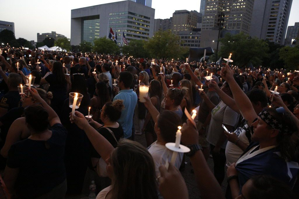 Participants held candles during a candlelight vigil hosted by the Dallas Police Association at Dallas City Hall on Monday.