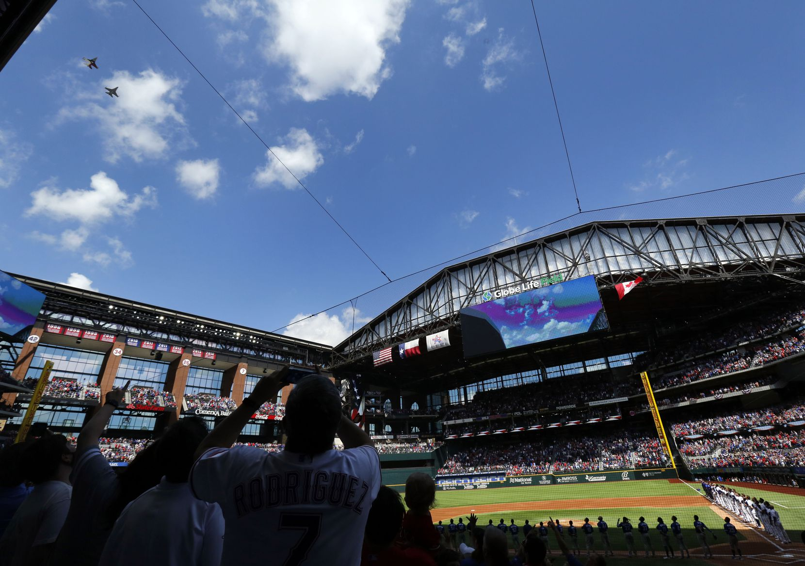 A pair of F-16 fighter jets flows over the the nearly sold-out Texas Rangers crowd following the national anthem on Opening Day at Globe Life Field in Arlington, Monday, April 5, 2021. The Rangers are facing the Toronto Blue Jays in the home opener. (Tom Fox/The Dallas Morning News)