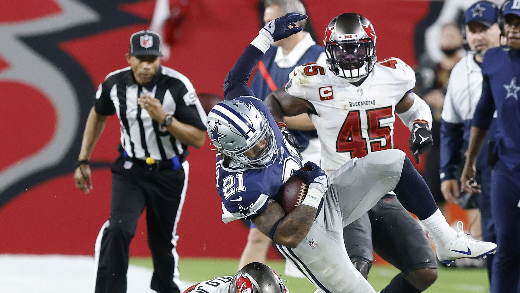 Dallas Cowboys running back Ezekiel Elliott (21) is knocked out of bounds by Tampa Bay Buccaneers safety Antoine Winfield Jr. (31) during a third quarter run at Raymond James Stadium in Tampa, Florida, Thursday, September 9, 2021. The Cowboys faced the Tampa Bay Buccaneers in the NFL season opener.