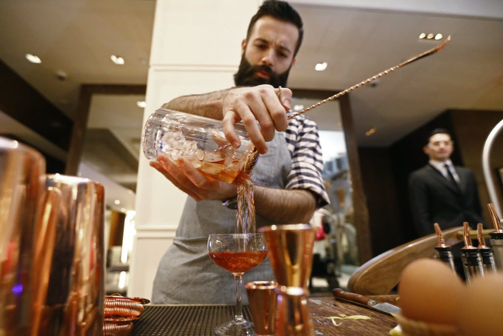 Bartender Ian Reilly mans a cocktail cart in the lobby of the Joule in Dallas January 9, 2016.