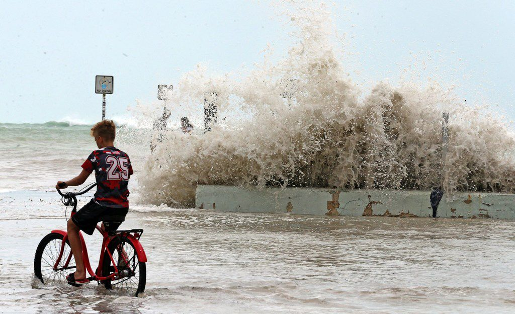 A Key West resident watches Saturday as waves crash onto a seawall in Key West, Fla..