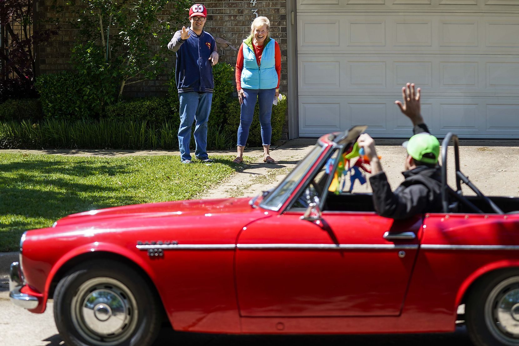 Alex Patterson and his mother, Connie Abookire, wave to birthday well-wishers outside the family's Plano home.