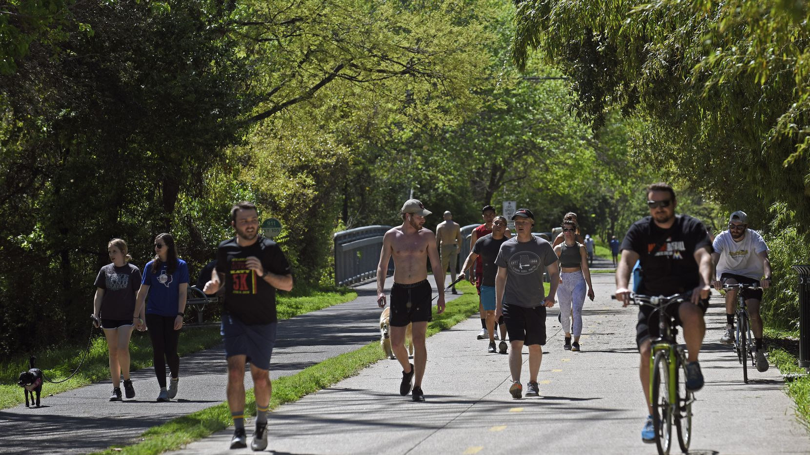 Groups of runners, cyclists and dog walkers use the Katy Trail near the Katy Trail Icehouse in Dallas, March 24, 2020. Dallas County Judge Clay Jenkins ordered residents of Dallas County to practice shelter in place. People can be out for essentials such as groceries, work and exercise, but must practice social distancing.