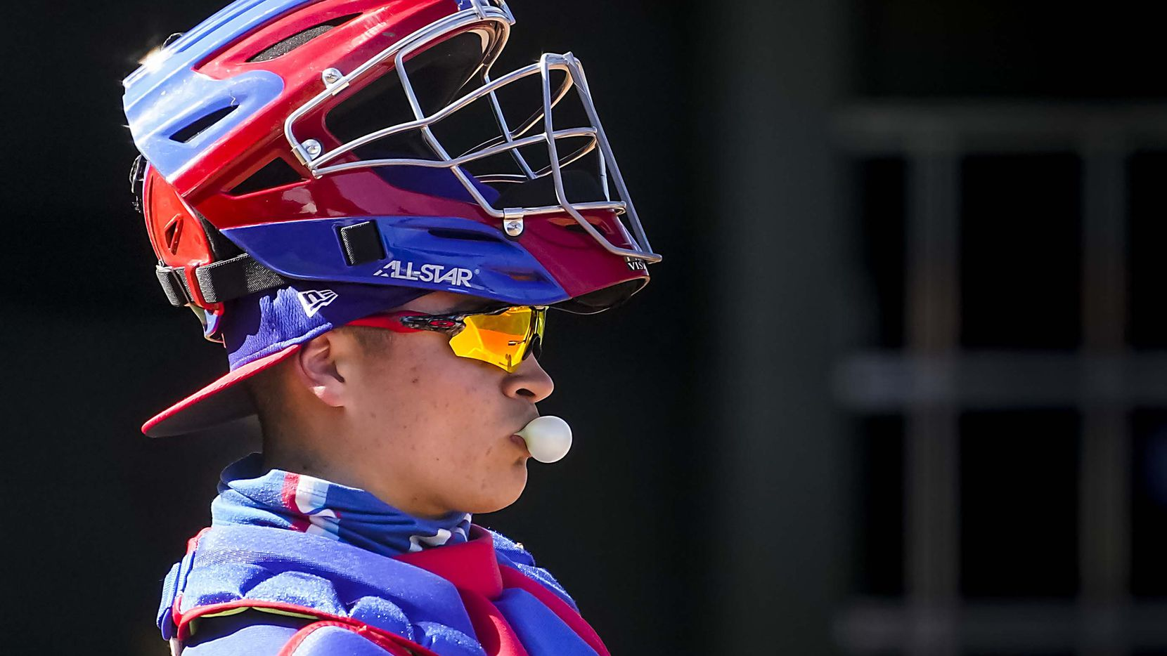 Texas Rangers catcher David Garcia blows a bubble between pitches during the sixth inning of a spring training game against the San Diego Padres at Surprise Stadium on Thursday, March 4, 2021, in Surprise, Ariz.