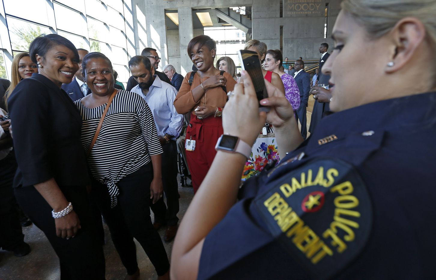 Dallas police Officer Diana Browning (right) takes pictures of new Dallas Police Chief U. Renee Hall (left) and Margertree Holmes during a meet-and-greet reception Monday.