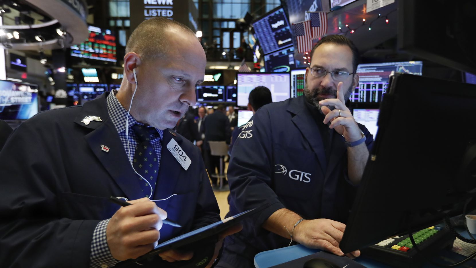 In this Dec. 11, 2019, file photo, trader Michael Urkonis, left, and specialist Anthony Matesic work on the floor of the New York Stock Exchange.