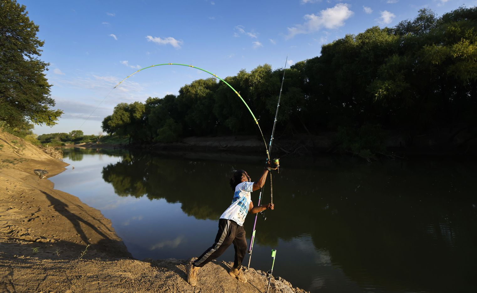 With the carp head as bait, Odell Allen casts his line for alligator gar on the Trinity River near the Westmoreland bridge, Monday, August 30, 2021.  Allen's viral videos of him catching 6-7 footers have made Dallas a popular spot for anglers all over the world who want to hook a gar. (Tom Fox/The Dallas Morning News)