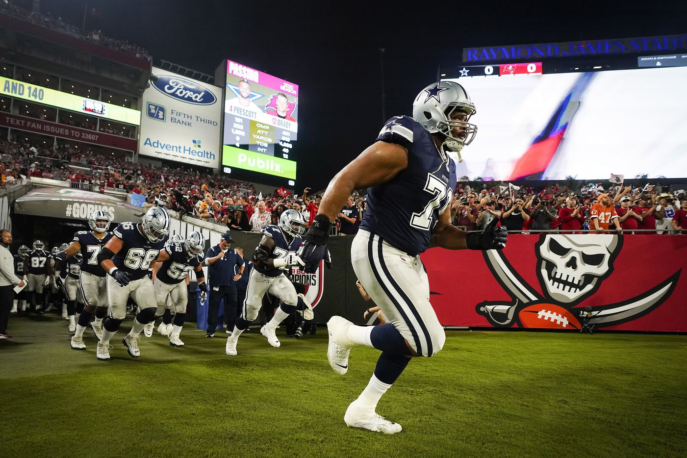 Dallas Cowboys offensive tackle La'el Collins (71) leads teammates onto the field before an NFL football game against the Tampa Bay Buccaneers at Raymond James Stadium on Thursday, Sept. 9, 2021, in Tampa, Fla. (Smiley N. Pool/The Dallas Morning News)