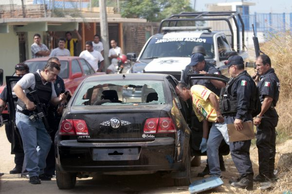 Mexican police examined a car containing a corpse and a human head in Acapulco on Jan. 20. The city is considered one of the world's most violent as drug cartels continue their battle for territory despite a federal crackdown.