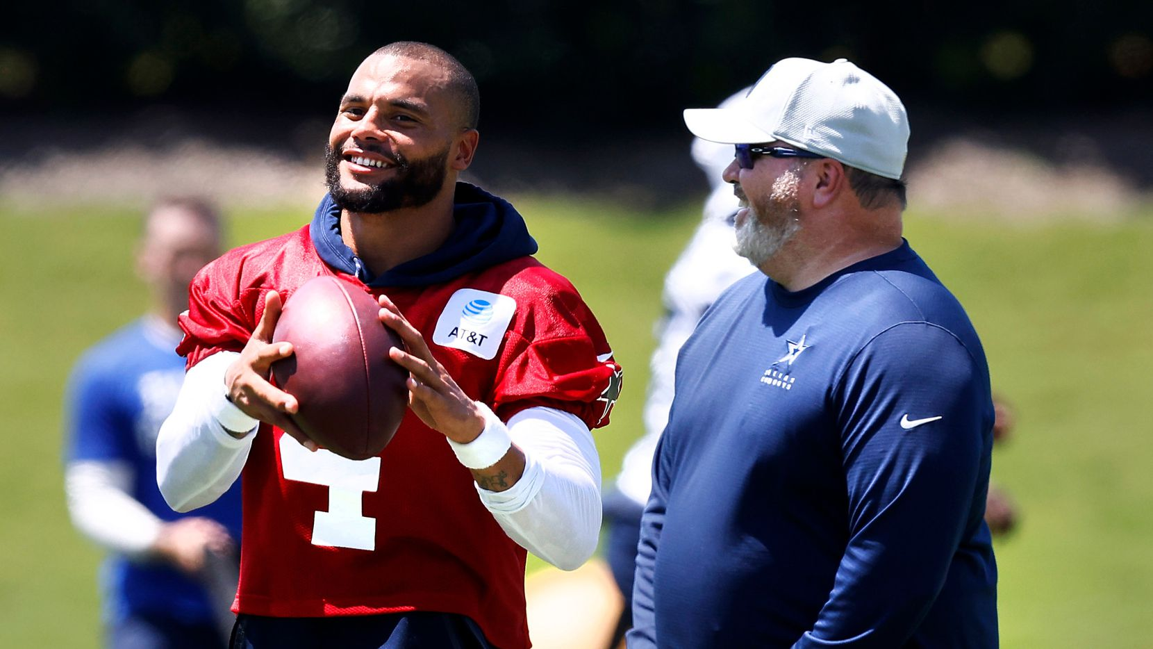 Dallas Cowboys head coach Mike McCarthy and  quarterback Dak Prescott (4) laugh following Training Camp practice at The Star in Frisco, Texas, Wednesday, August 25, 2021.