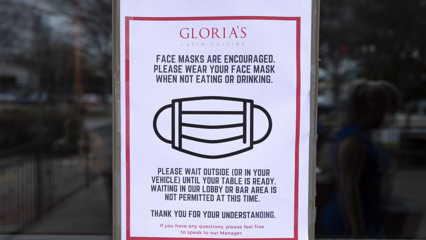 Signage outside of Gloria's Latin Cuisine restaurant at the Bishop Arts District in Dallas, on the first day the mask mandate and occupancy limits are lifted, on Wednesday. The city has started a database and is asking businesses to let residents know if they will be requiring masks.