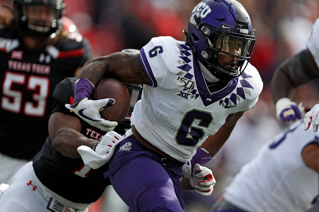 TCU's Darius Anderson (6) breaks a tackle while running with the ball during the first half of an NCAA college football game against Texas Tech, Saturday, Nov. 16, 2019, in Lubbock, Texas.