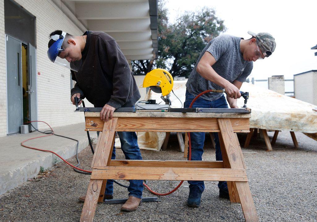 Diego Reyes (left) and Alvaro Luna Jr. grind their welds during shop class at Skyline High School.
