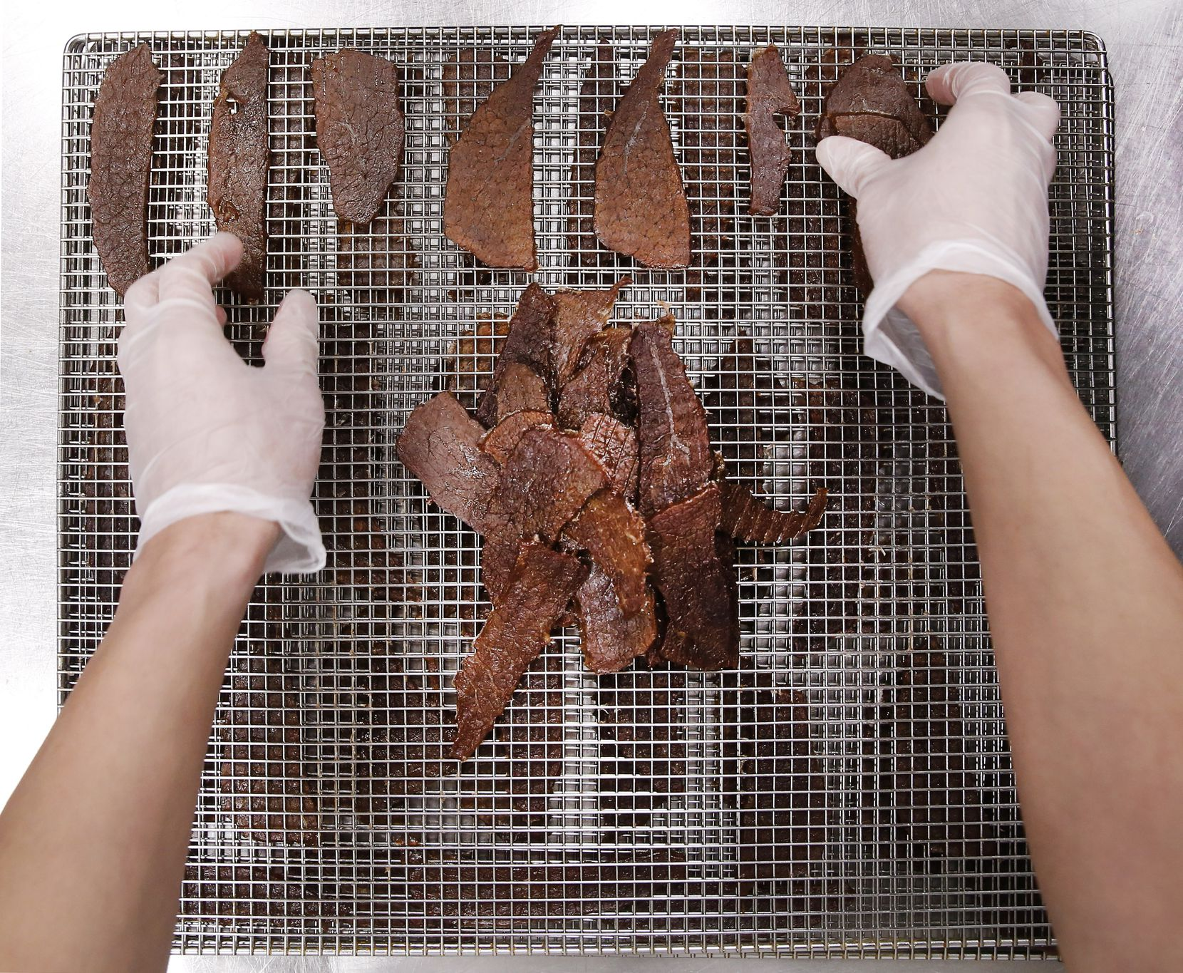 Frick Chanthorn removes warm beef jerky slices from the dehydration unit and piles them up before flash frying them at Saap Lao Kitchen.