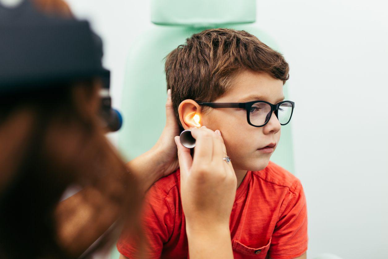 Un niño sujeto a un examen en su oído derecho.