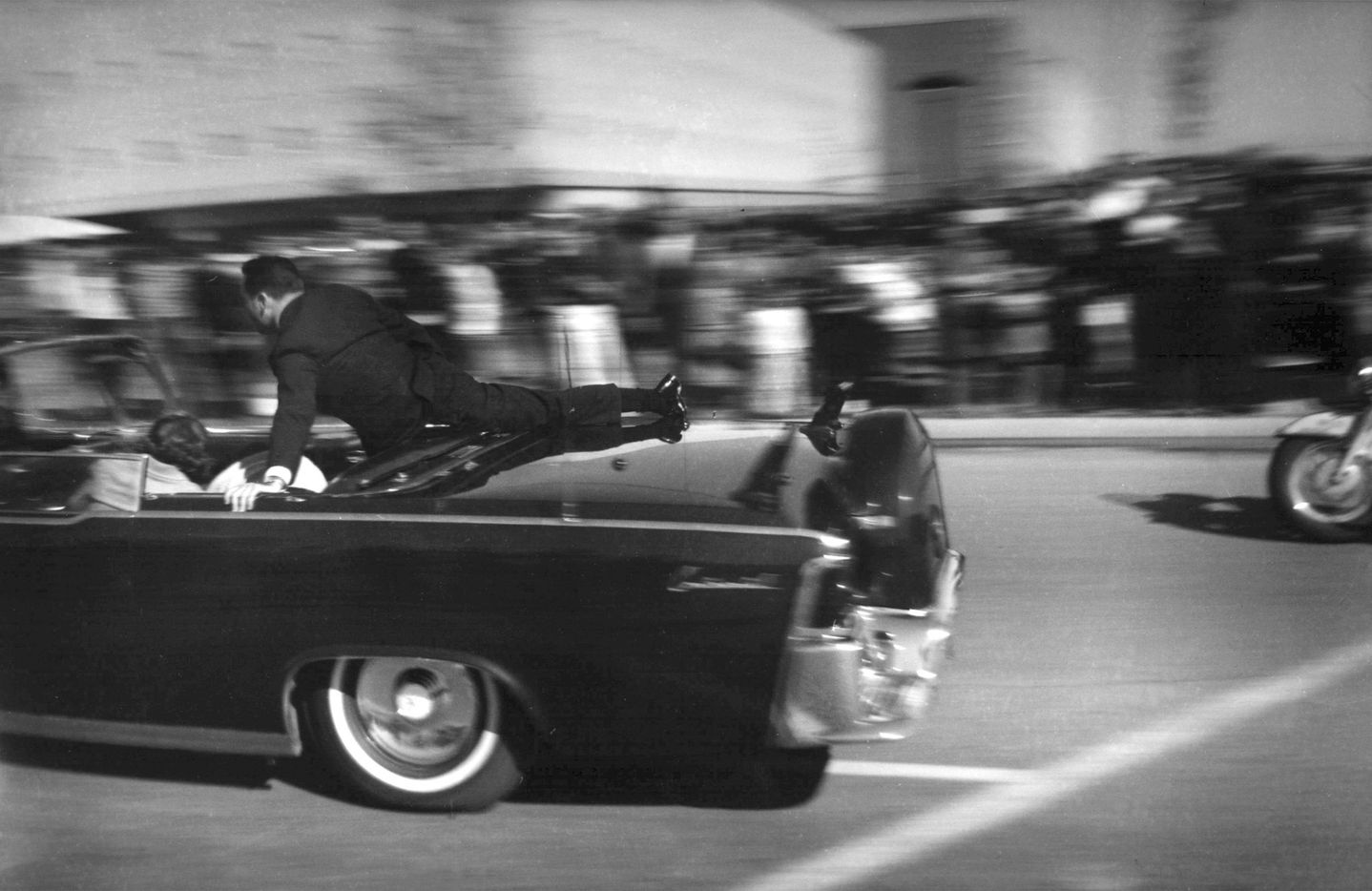 The limousine carrying a mortally wounded president races toward the hospital seconds after he was shot in Dallas. Secret Service agent Clinton Hill is riding on the back of the car.