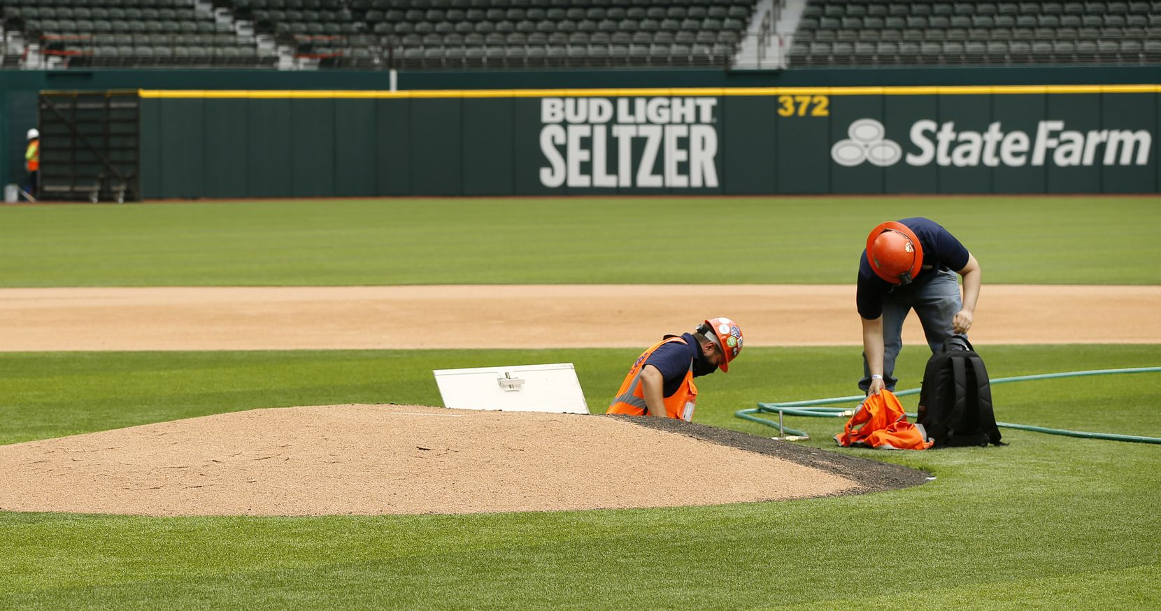Construction workers climb out of the pitching mound at the newly completed Globe Life Field in Arlington, Wednesday, May 20 2020. A door at the back of the mound leads to a 3-4 foot crawl space for the circular dirt hill to be lowered for non-baseball events. (Tom Fox/The Dallas Morning News)