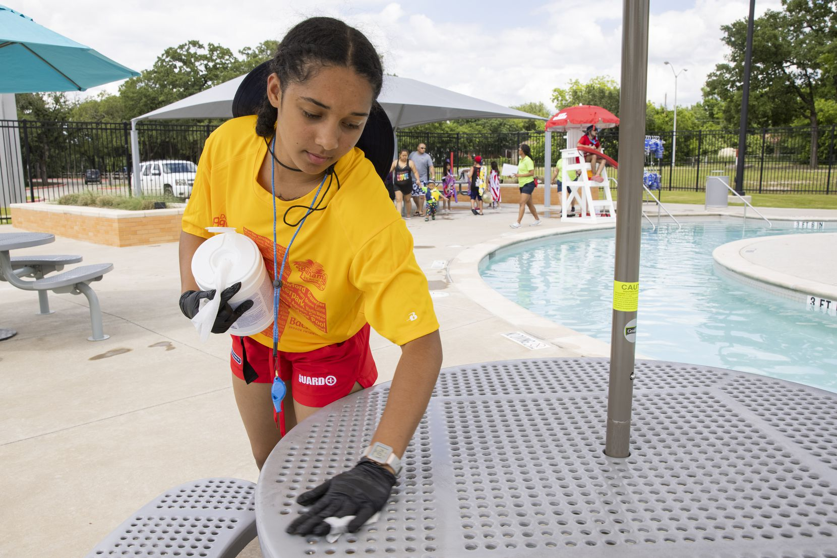 Lifeguard Jaedan Freeman, 17, wipes down tables with disinfectant wipes during a break at the Cove Aquatic Center at Crawford, in Dallas' Pleasant Grove community, on Saturday, May 29, 2021.