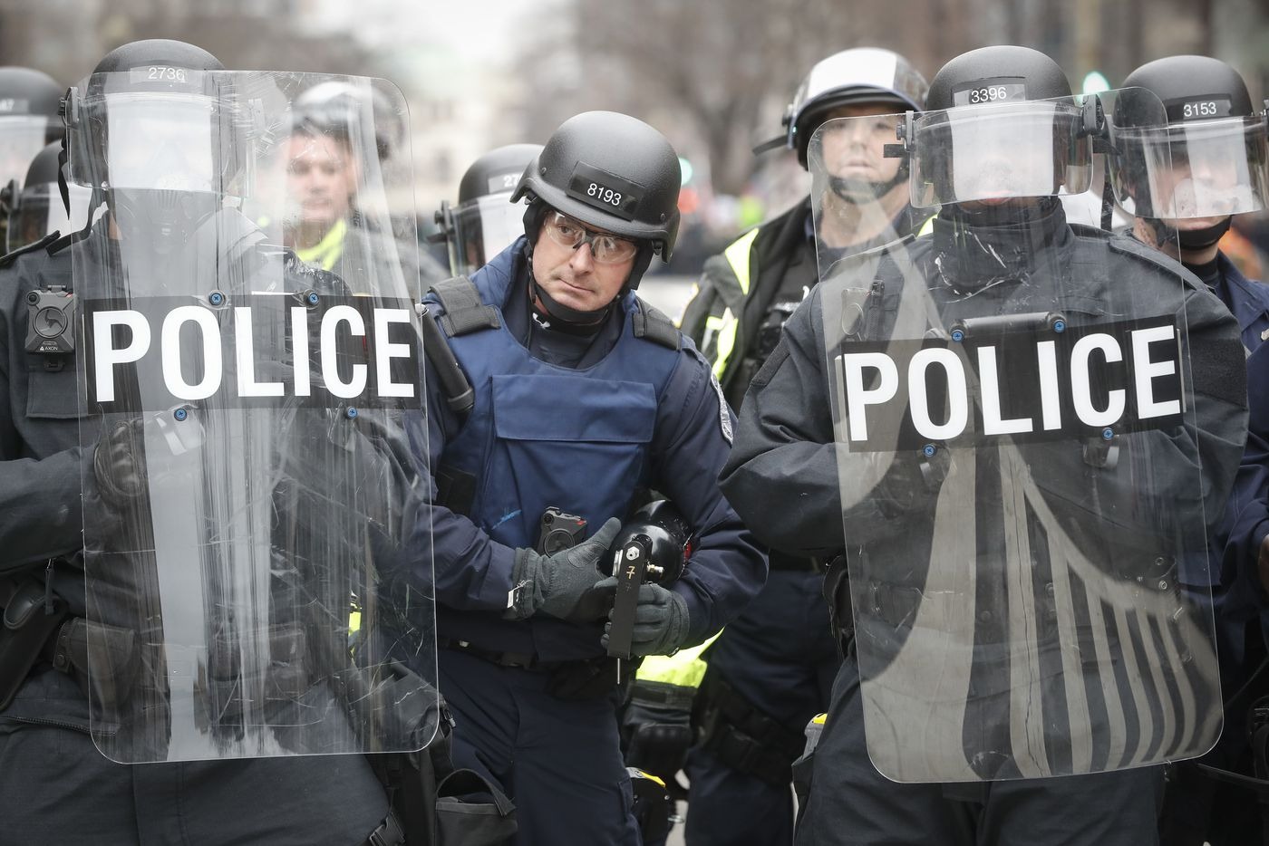A police officer carrying a pepper spray gun stands between riot shields during a demonstration after the inauguration of President Donald Trump, Friday, Jan. 20, 2017, in Washington.