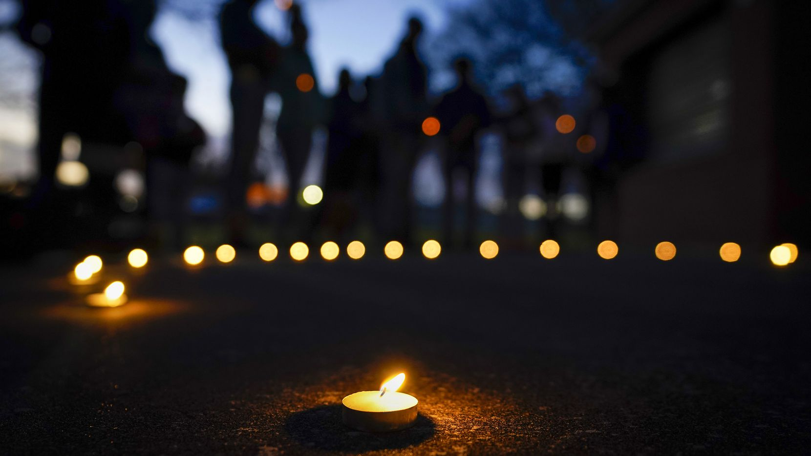 """Mourners gather for a vigil for Marc """"Flea"""" Strickland, the 18-year-old victim of a shooting at Dallas ISD basketball game, as the sun sets at Bushman Park on Sunday, Jan. 19, 2020."""