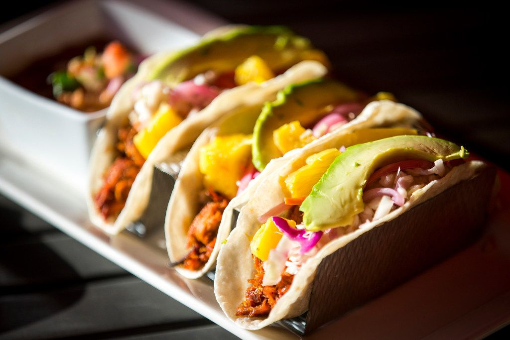 Avocado slices and pineapple chunks top the Al Pastor Tacos at Beto and Son restaurant in Trinity Groves.