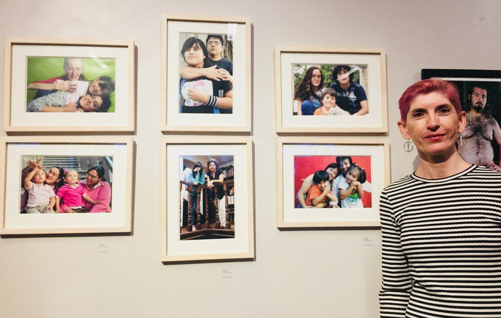 The photographer Olivia Peregrino poses with her photos during the art show MaricónX featuring Hispanic LGBT artists at the Oak Cliff Cultural Center on May 4.