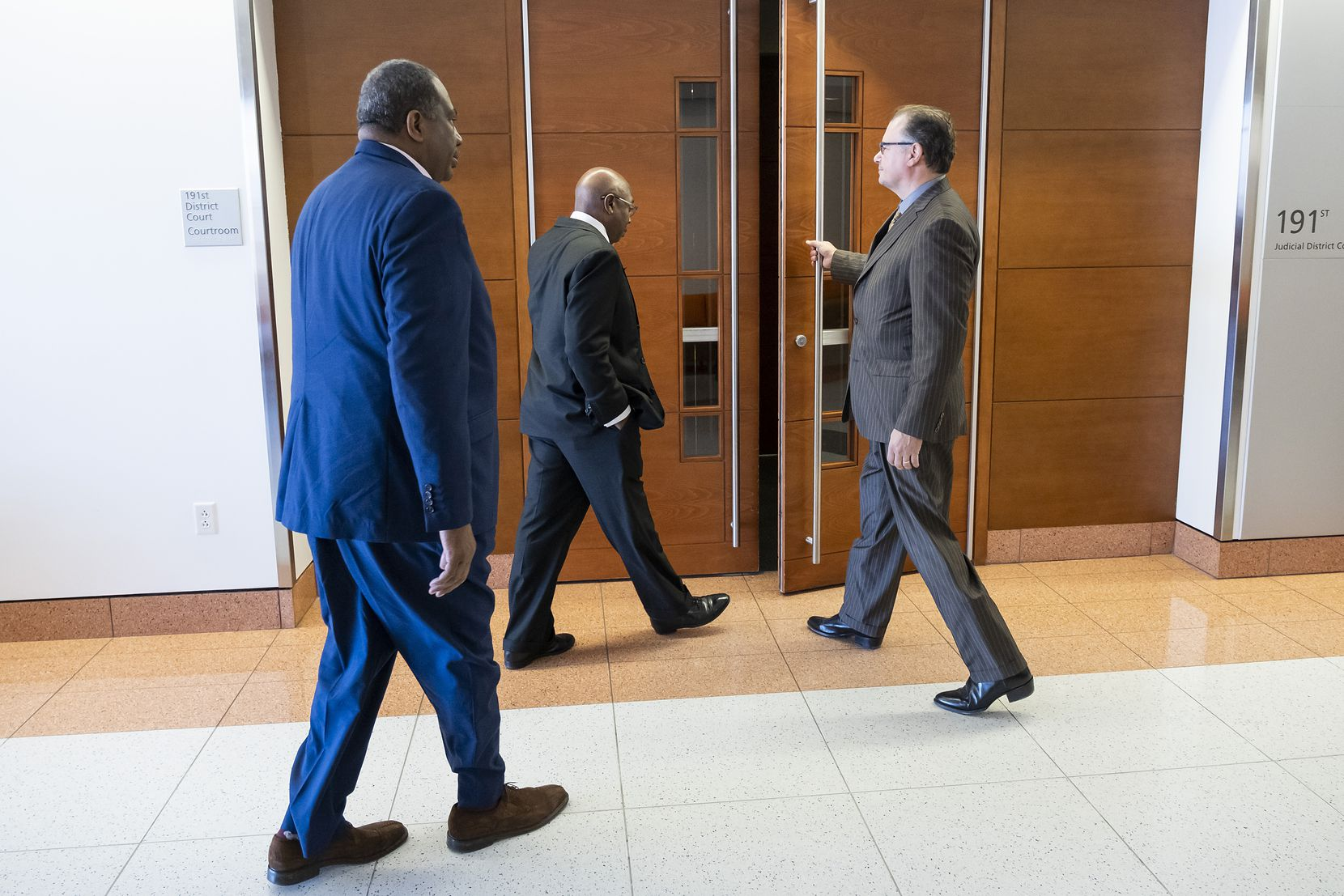 Chris Caso, interim Dallas city attorney (right), holds the door for Dallas council member Tennell Atkins and State Sen. Royce West to enter a hearing at Judge Gena Slaughter's courtroom at the  George L. Allen, Sr. Courts Building on Thursday, March 21, 2019. A hearing was held Thursday on the fate of what has become known as Shingle Mountain in southeast Dallas.