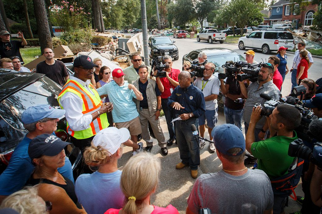 Houston Mayor Sylvester Turner talks with residents on a street of homes damaged by flooding from Hurricane Harvey in the Fosters Mill Village subdivision of the Kingwood area on Sept. 4, 2017.