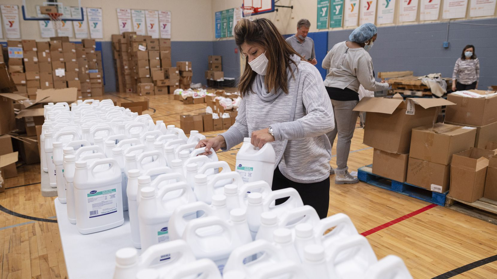 Irene Johnson, district executive director for Frisco Family YMCA and Plano Family YMCA, organizes gallons of disinfectant cleaner as workers packed essentials goods for families in need at the Moorland Family YMCA in Dallas. MacKenzie Scott, author and philanthropist, donated $10 million to the YMCA of Metropolitan Dallas.