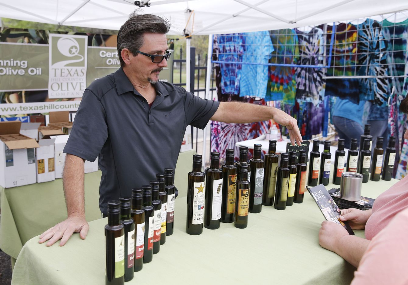 Texas Hill Country Olive Company's Byron Swindle explains the different products they offers a variety of products during opening day for the Tyler Street Market run by Good Local in Dallas on Saturday, March 18, 2017.