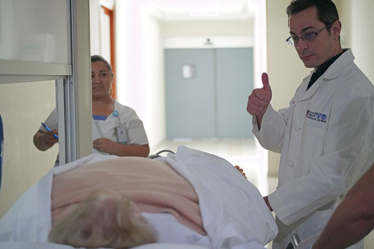 """Dr. Thomas Parisi checks in on patient Donna Ferguson after her surgery.  """"Everything went great,"""" Parisi told her. (Rocco Saint-Mleux for Kaiser Health News)"""