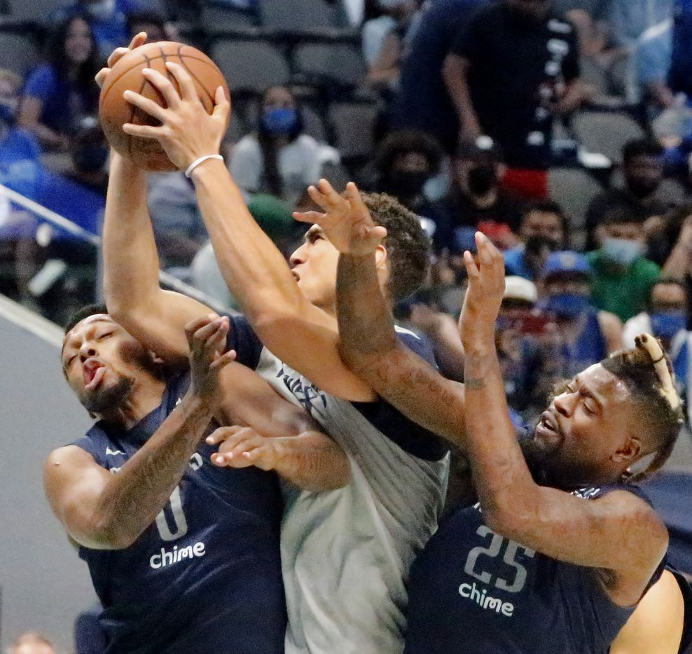 Dallas Mavericks center Dwight Powell (7) pulls down a rebound as he battles between Dallas Mavericks forward Sterling Brown (0) and Dallas Mavericks forward Reggie Bullock (25) as the Dallas Mavericks held their Mavs Fam Jam, a scrimmage free to the public at the American Airlines Center in Dallas on Sunday, October 3, 2021. (Stewart F. House/Special Contributor)