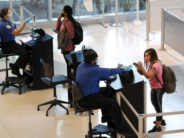 Transportation Security Administration agents helped travelers as they cleared security for flights out of Love Field in Dallas in June.