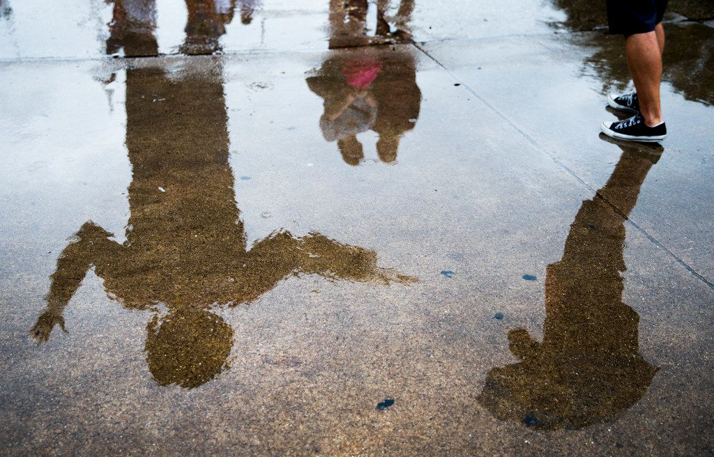 Big Tex is reflected in a rain puddle as fair goers take photos the State Fair of Texas.