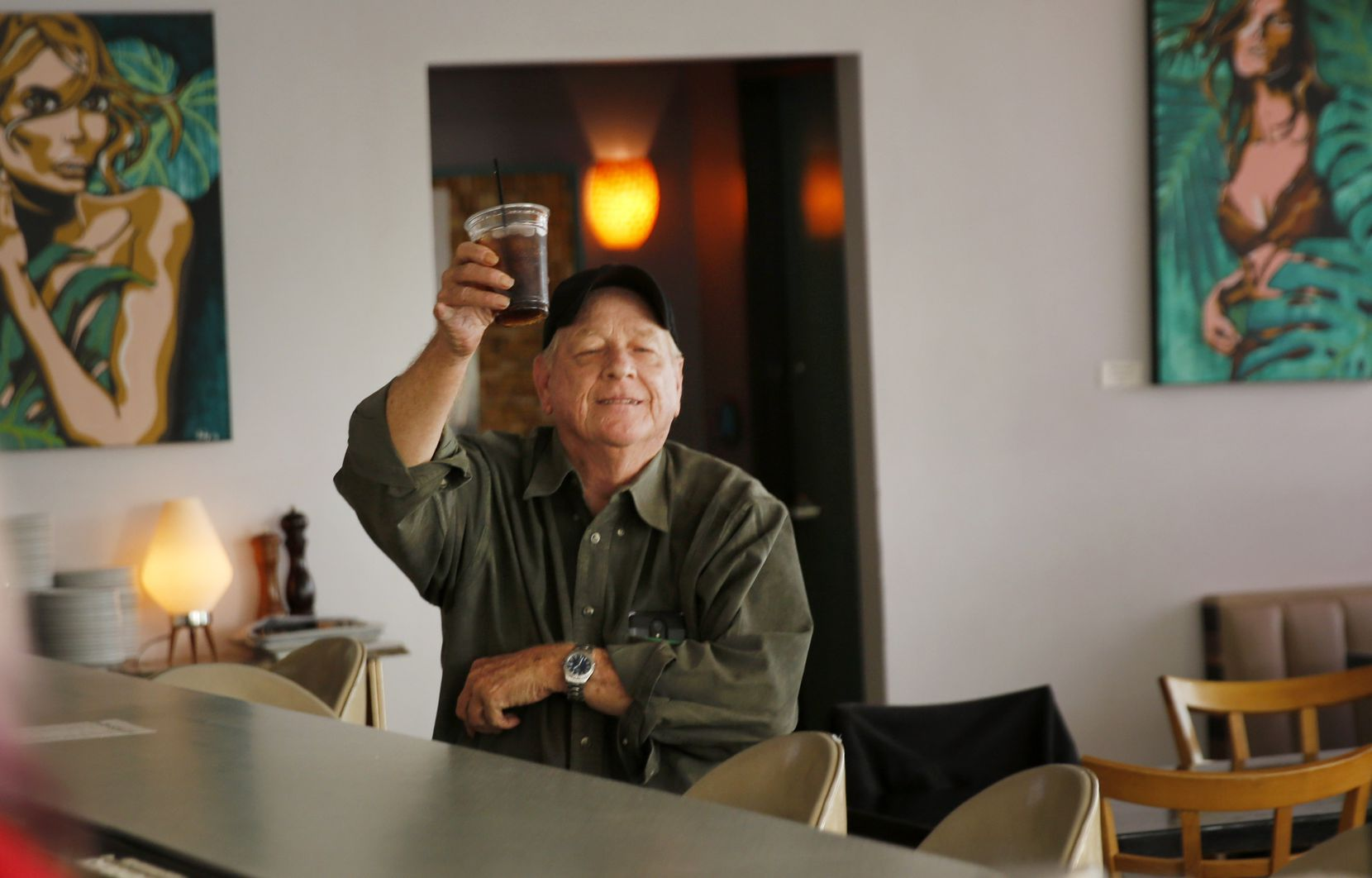 Longtime patron Jim Harper raised his glass as a nod to the final day of hanging out in Nova, a popular Oak Cliff neighborhood restaurant and bar that's had to close for sit-down service because of the coronavirus, on Saturday, March 21, 2020. (Tom Fox/The Dallas Morning News)