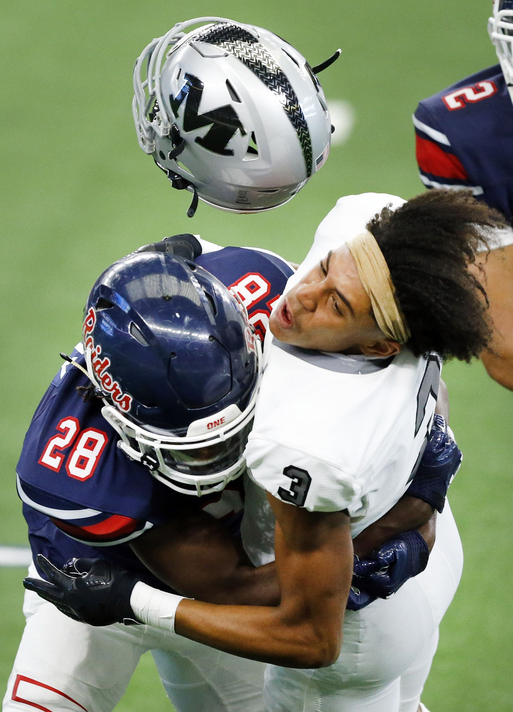 Denton Ryan defensive back Kaden Kelly (28) puts a hit on Arlington Martin receiver Cydd Ford (3), forcing his helmet to fly off on an overthrown pass in first half at AT&T Stadium in Arlington, Friday, September 25, 2020. No penalty was assessed on the play. (Tom Fox/The Dallas Morning News)
