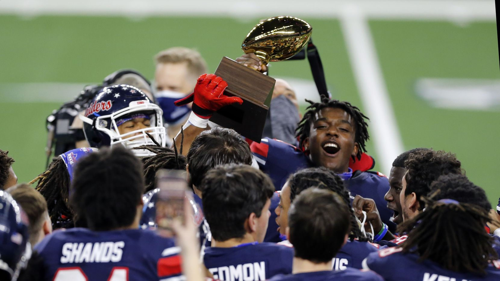 Members of the Denton Ryan football team celebrate with the trophy after winning the Class 5A Division I state semifinal football playoff game against Mansfield Summit High at AT&T Stadium in Arlington on Friday, January 8, 2021. Ryan won 49-35. (John F. Rhodes / Special Contributor)