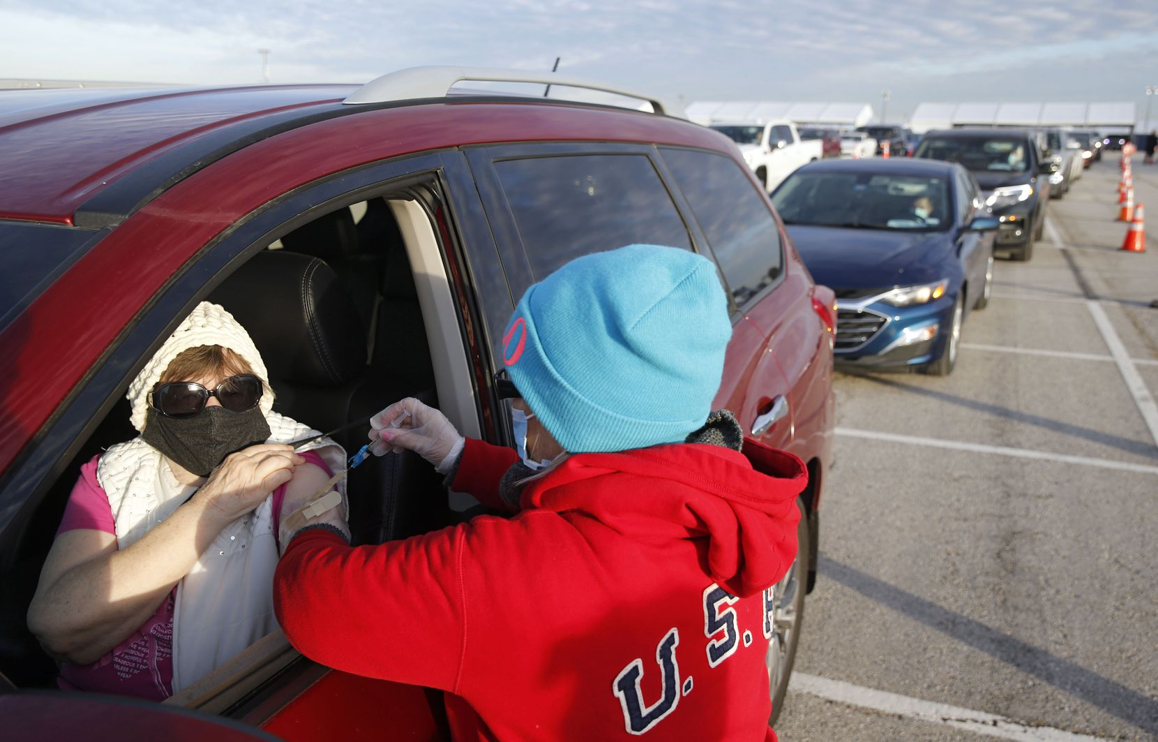 Donna Bergman of Flower Mound receives a COVID-19 vaccination from Penny Mayo at a drive-through vaccination clinic at Texas Motor Speedway in Fort Worth.