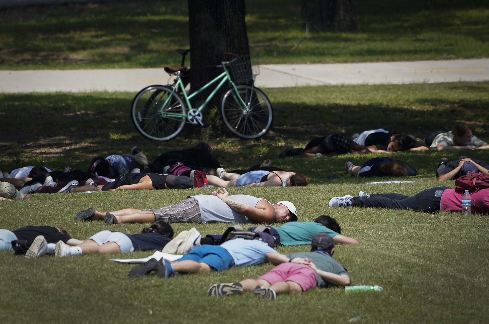 A group of demonstrators lies in the grass, many with their hands behind their backs, at Flagpole Hill as protests continue after the death of George Floyd on Tuesday, June 2, 2020, in Dallas.