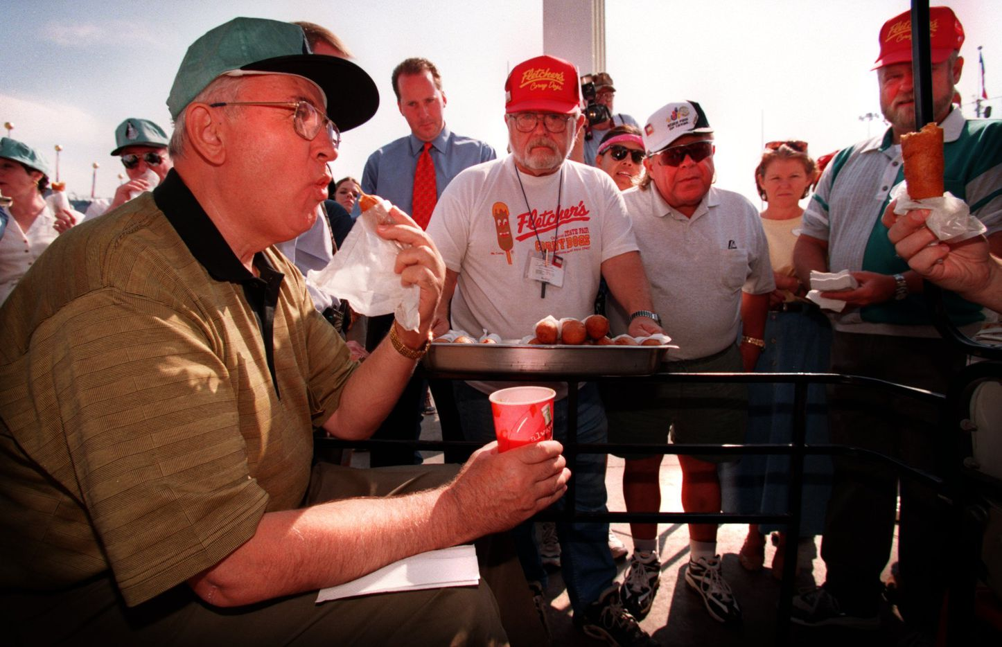 Former Soviet Union President Mikhail  Gorbachev (left) enjoys a Corny Dog, as Fletcher family members  and employees, including Greg True (center with white beard and  glasses and tray of dogs), Skip Fletcher (center with white hat/ shirt and sunglasses) and Bill Fletcher (right with red hat and  green vest) watch with anticipation.