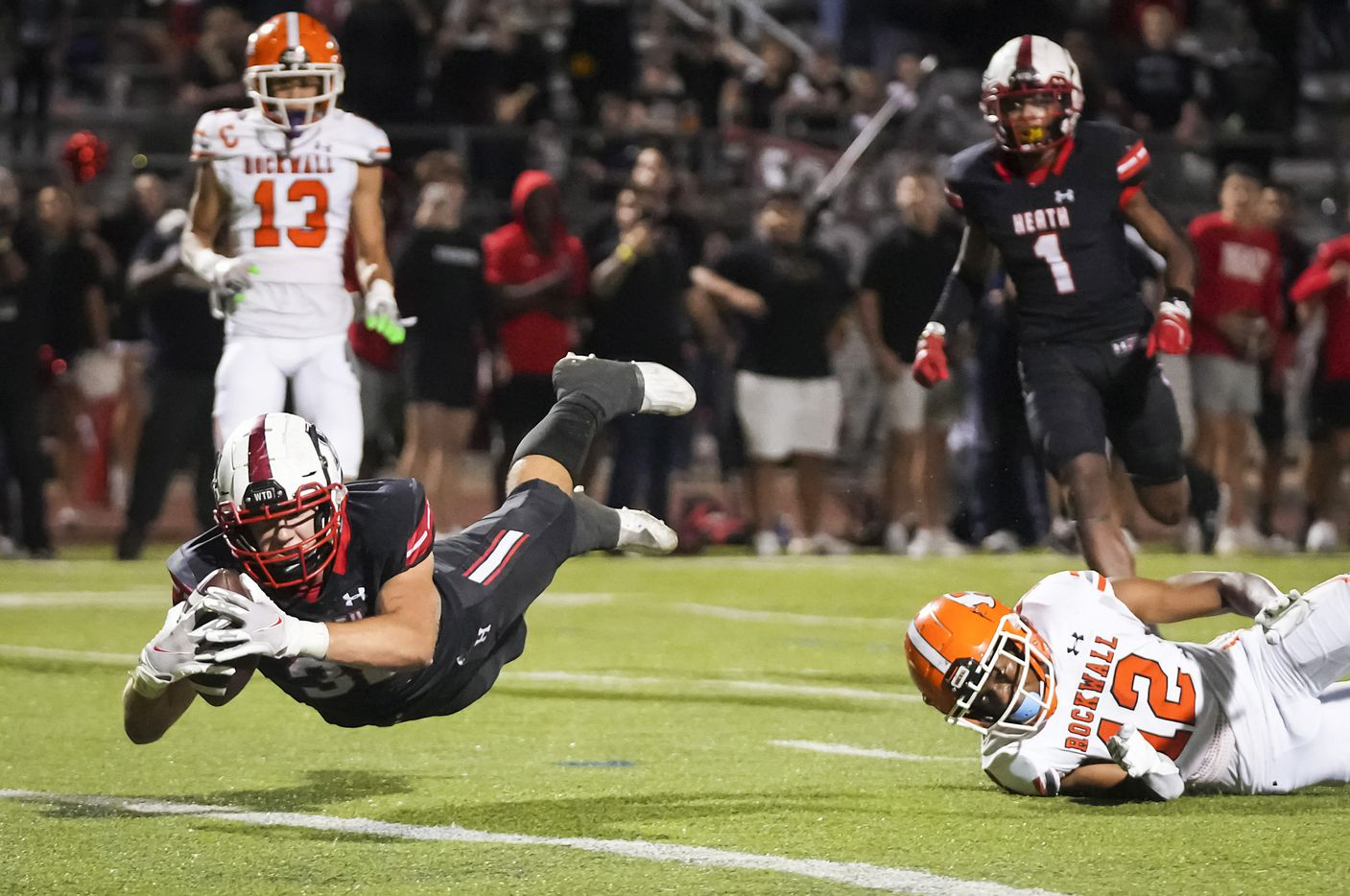 Rockwall-Heath tight end  Lance Mason (38) dives for the end zone to score a 21-yard touchdown pass to give the Hawks the lead with :18 seconds left as Rockwall defensive back Kevin Cunningham (12) defends during the second half of a District 10-6A high school football game at Wilkerson-Sanders Stadium on Friday, Sept. 24, 2021, in Rockwall.  Rockwall-Heath won the game 79-71 in double overtime.