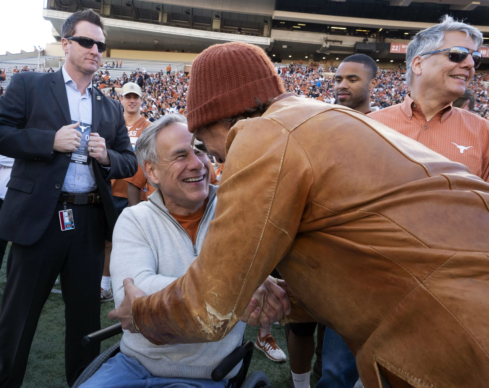 Matthew McConaughey greeted Gov. Greg Abbott at an April 2019 University of Texas Orange and White spring football game in Austin.