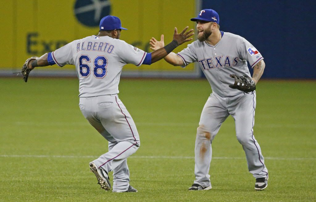 FILE - Texas Rangers third baseman Hanser Alberto (68) and Texas Rangers first baseman Mike Napoli (25) celebrate after the final out of a 6-4 win after 14 innings in Game 2 of the ALDS between the Rangers and Toronto Blue Jays  at Rogers Centre in Toronto, Canada on Friday, October 9, 2015. (Louis DeLuca/The Dallas Morning News)