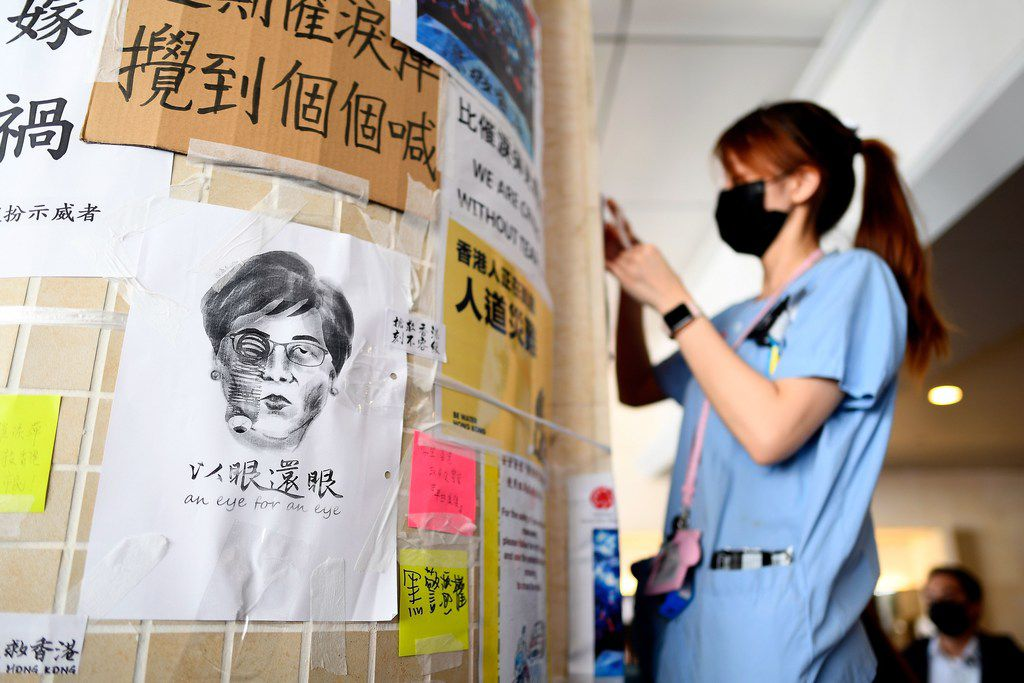 "A nurse sticks posters next to a caricature of  Chief Executive Carrie Lam during a solidarity protest at the Queen Mary Hospital in Hong Kong on Aug. 13, 2019. Hong Kong's leader warned pro-democracy protesters against heading down ""a path of no return,"" but they responded with a fresh rally at the city's airport a day after demonstrators triggered an unprecedented shutdown."