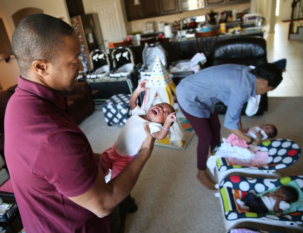 Gregory Hill holds one of his newborn triplets, Lena, while wife Kisha tends to Gemma and Gregory at their home in Fort Worth on March 7, 2018.