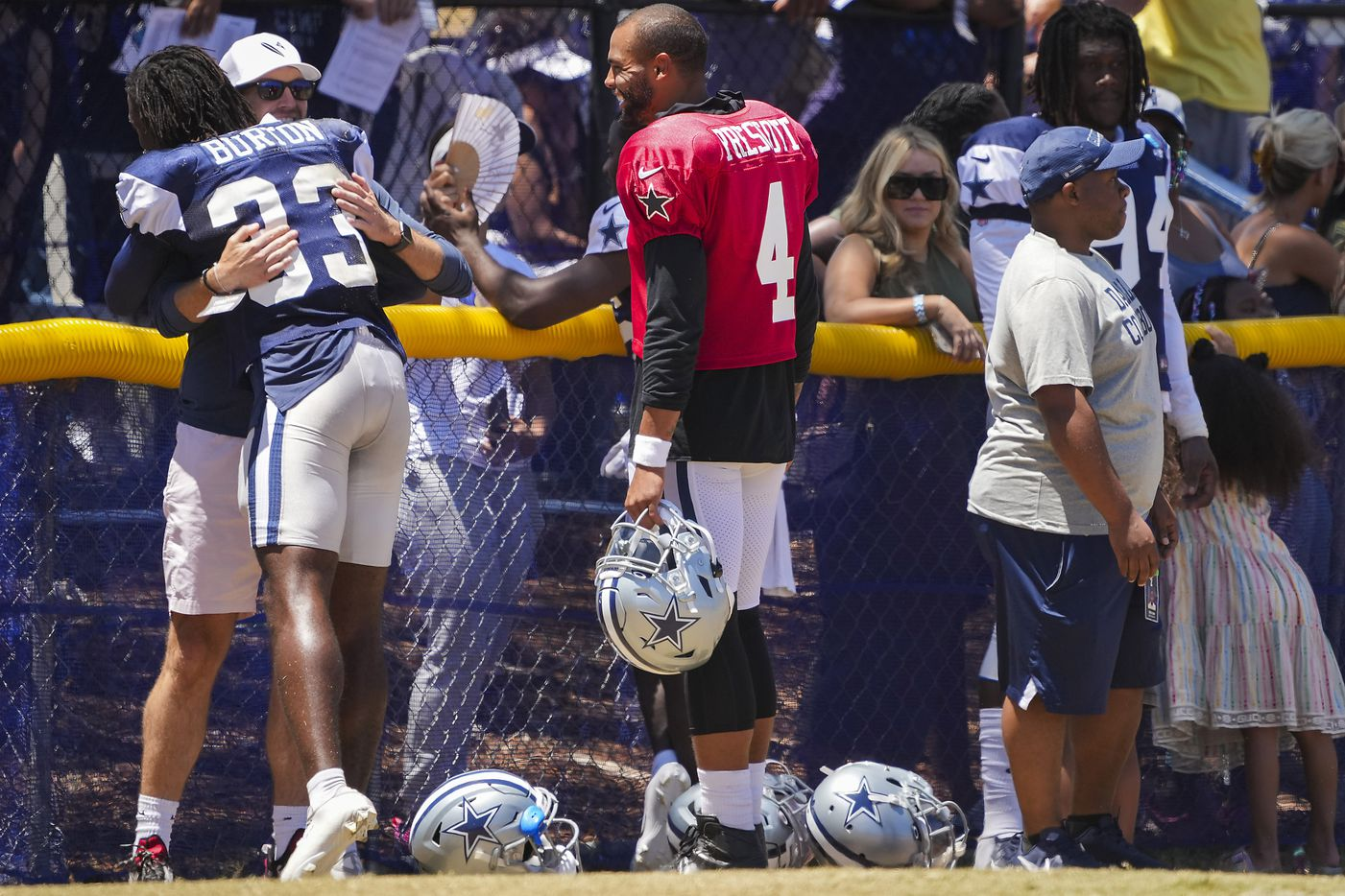 Dallas Cowboys quarterback Dak Prescott (4), cornerback Deante Burton (33) and defensive end Randy Gregory (94) spend time with family and friend after a practice at training camp on Sunday, Aug. 1, 2021, in Oxnard, Calif.